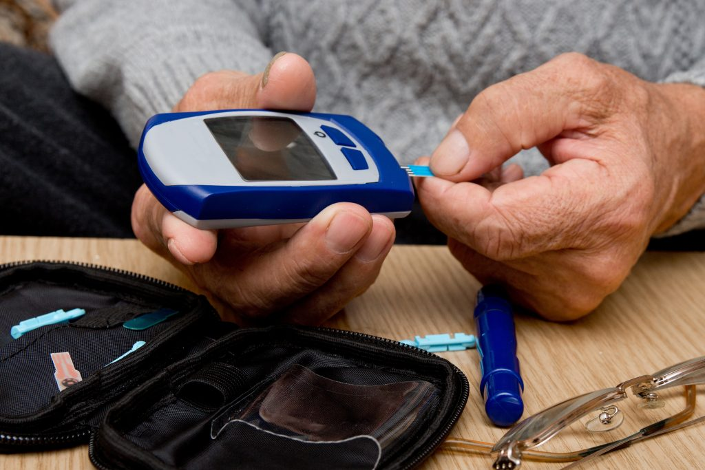 Concept diabetes in the elderly retired. Senior man with glucometer checking blood sugar level at home. Learn to use a glucometer